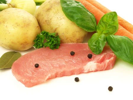 Slice of raw pork with potatoes, carrots and herbs photo