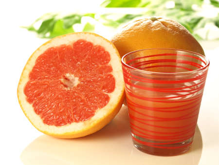 Succulent fresh pink grapefruit with glass of juice photo