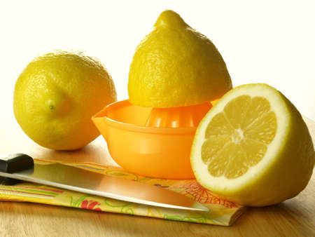 Squeezing three fresh lemons on the cutting board photo
