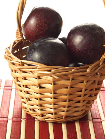 Plums in wicker basket on isolated background Stock Photo - 13193391