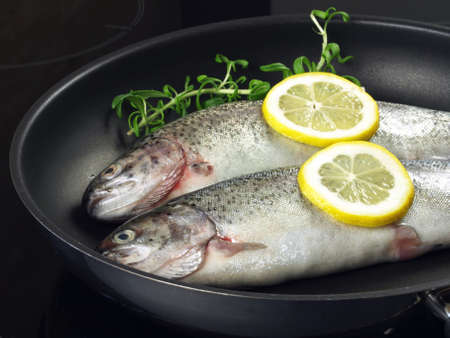 Trout with rosemary and lemon slices on frying pan  photo