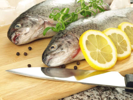 Two fresh trouts on cutting board for preparation photo