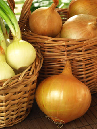 spring onions: Closeup of variety of onions in wicker baskets Stock Photo
