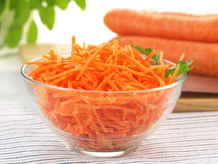 Bowl with fresh grated carrot on a napkin Stock Photo