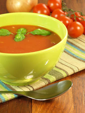 Delicious tomato soup with basil in bowl photo