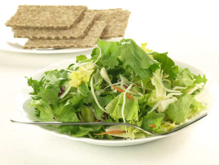 Light healthy salad and crispbread on isolated background photo