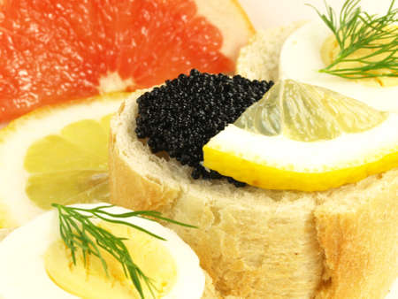 Bread, caviar, egg, and slices of citrus photo