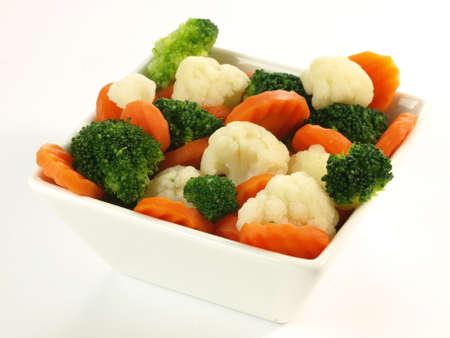 brocoli: Tazón de verduras hervidas en el fondo aislado