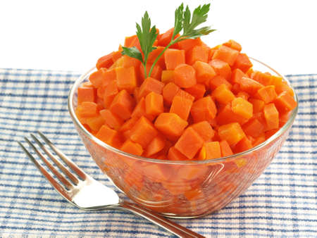 Bowl of chopped carrot on tablecloth on isolated background photo