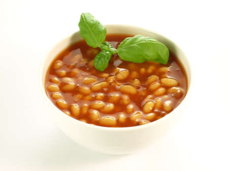 Bowl of baked beans with basil on isolated background photo