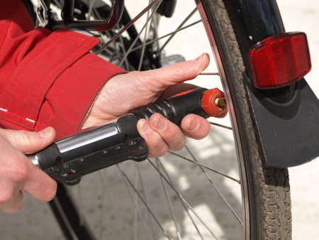 Closeup of mechanic pumping a bicycle tire photo