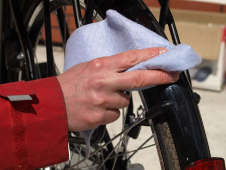Man cleaning his bike with a cloth photo