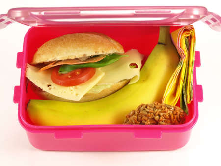 Pink lunch box with sandwich, banana and cookie photo