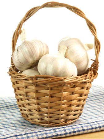 Wicker basket with garlic heads on isolated background photo