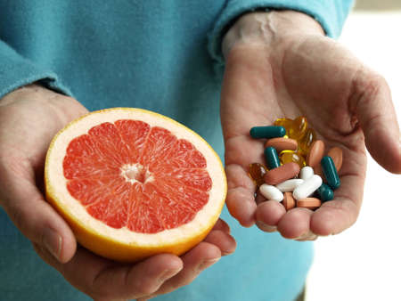 health care decisions: Woman holding a fruit and handful of pills Stock Photo
