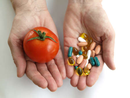 Man holding a vegetable and handfull of supplements