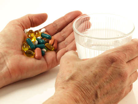 Person taking a handfull of drugs on isolated background
