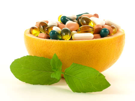 and vitamin: Fruits full of vitamin pills on isolated background.  Stock Photo