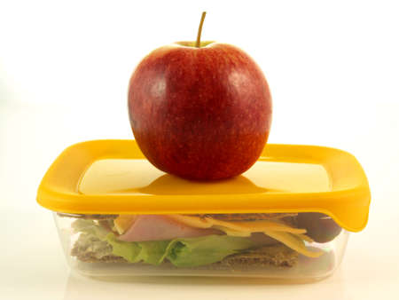 Closed box with sandwich and apple on isolated background photo