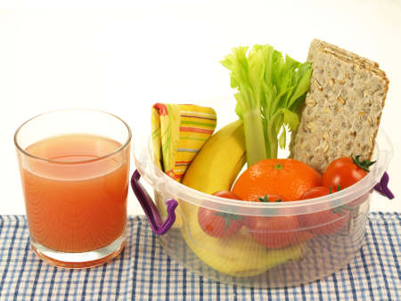 lunch box: Orange juice and plastic container with healthy snacks