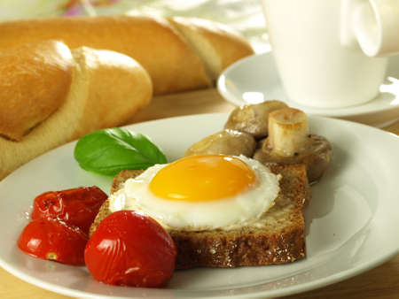 sunny side up: Easter sunny side up egg on a slice of bread with tomatoes with a French loaf.