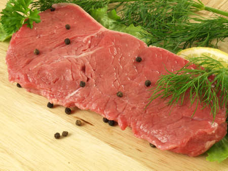 Raw steak with dill, lemon and lettuce photo