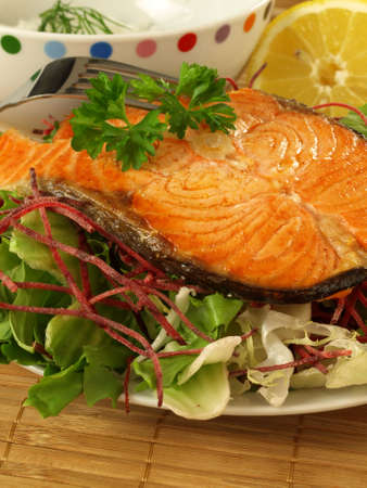 Slice of salmon with salad photo