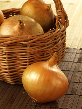 close up of onions in a basket: Organic fresh onions in a wicker basket Stock Photo