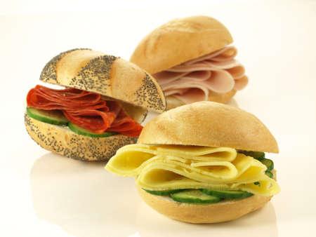 jamon y queso: Tres rollos de salami, queso y jamón, aislado Foto de archivo