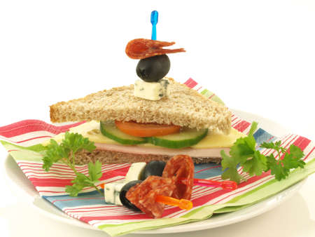 Plate with sandwich and snacks on white background photo