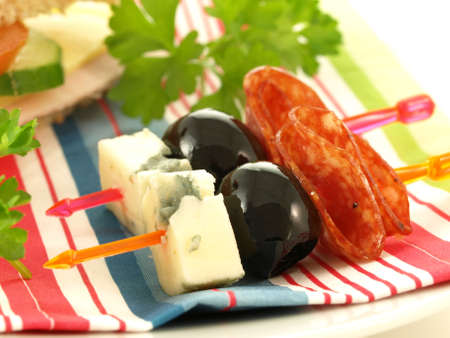 Close up of olives, cheese and salami on toothpicks photo