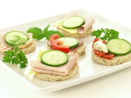 Five round sandwiches served on white plate photo