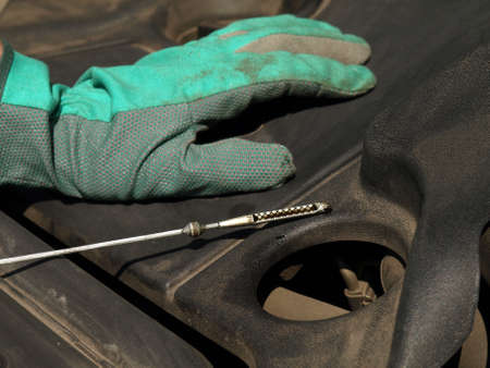 Car service: checking oil in engine, closeup photo