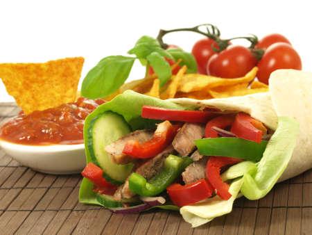 fajita: Rolled fajita with salsa on wooden pad Stock Photo