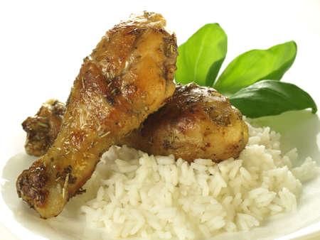 Golden chicken legs with rice on white background photo