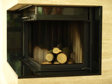 Modern fireplace loaded with heap of wooden logs photo