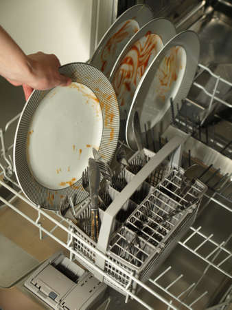 Putting dirty plates in the dishwasher after dinner photo