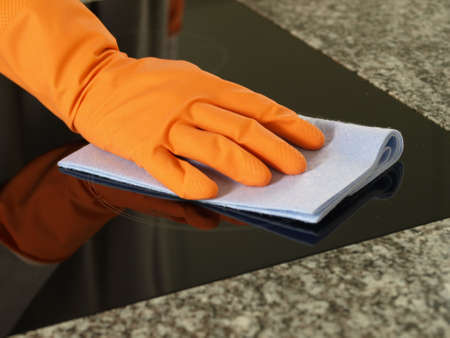 Hand in glove cleaning kitchen cooking top Stock Photo - 13805059