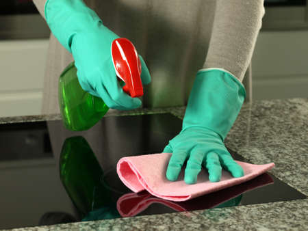 Woman's hands cleaning kitchen top in gloves      photo