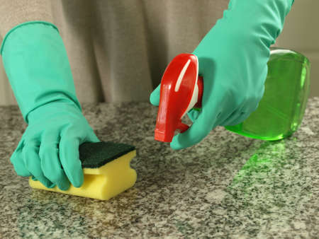 Housewife cleaning up a kitchen top with sponge and spray photo