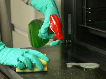 cleaning up: Hands in gloves cleaning up oven with sponge and detergent Stock Photo