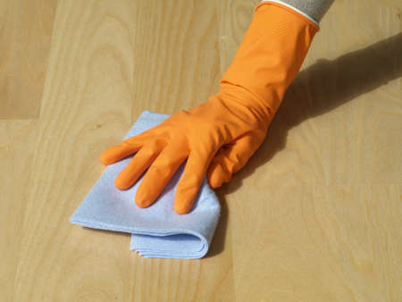 cleaning floor: Hand in glove with rag cleaning up wooden floor