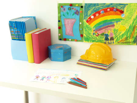 Books, crayons and toys on childrens desk photo