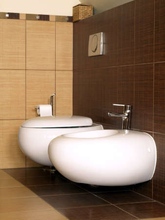 Toilet and bidet in brown-beige bathroom, closeup, vertical photo