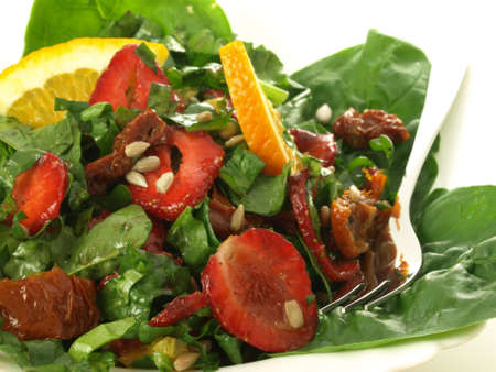 Salad with spinach, strawberries and orange, closeup photo