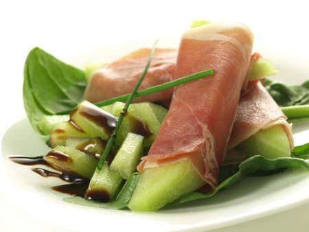 Melon and prosciutto appetizer with balsamic vinegar photo