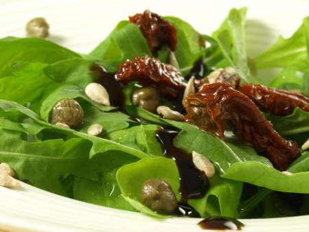 legumbres secas: Detalle de ensalada de rúcula salvaje con tomates secados al sol