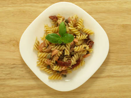 Fusilli pasta with pieces of salmon fish on plate photo