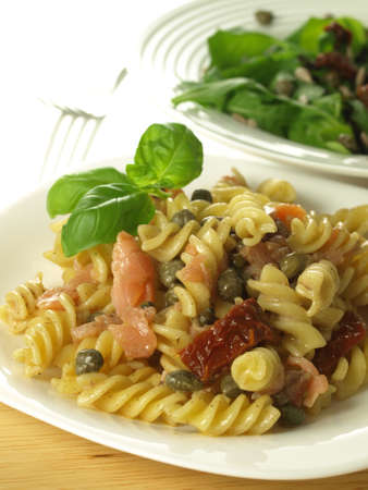 Pasta with salmon and vegetables and salad photo
