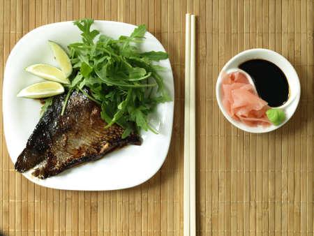 Fried salmon, marinated ginger, soy sauce and arugula photo